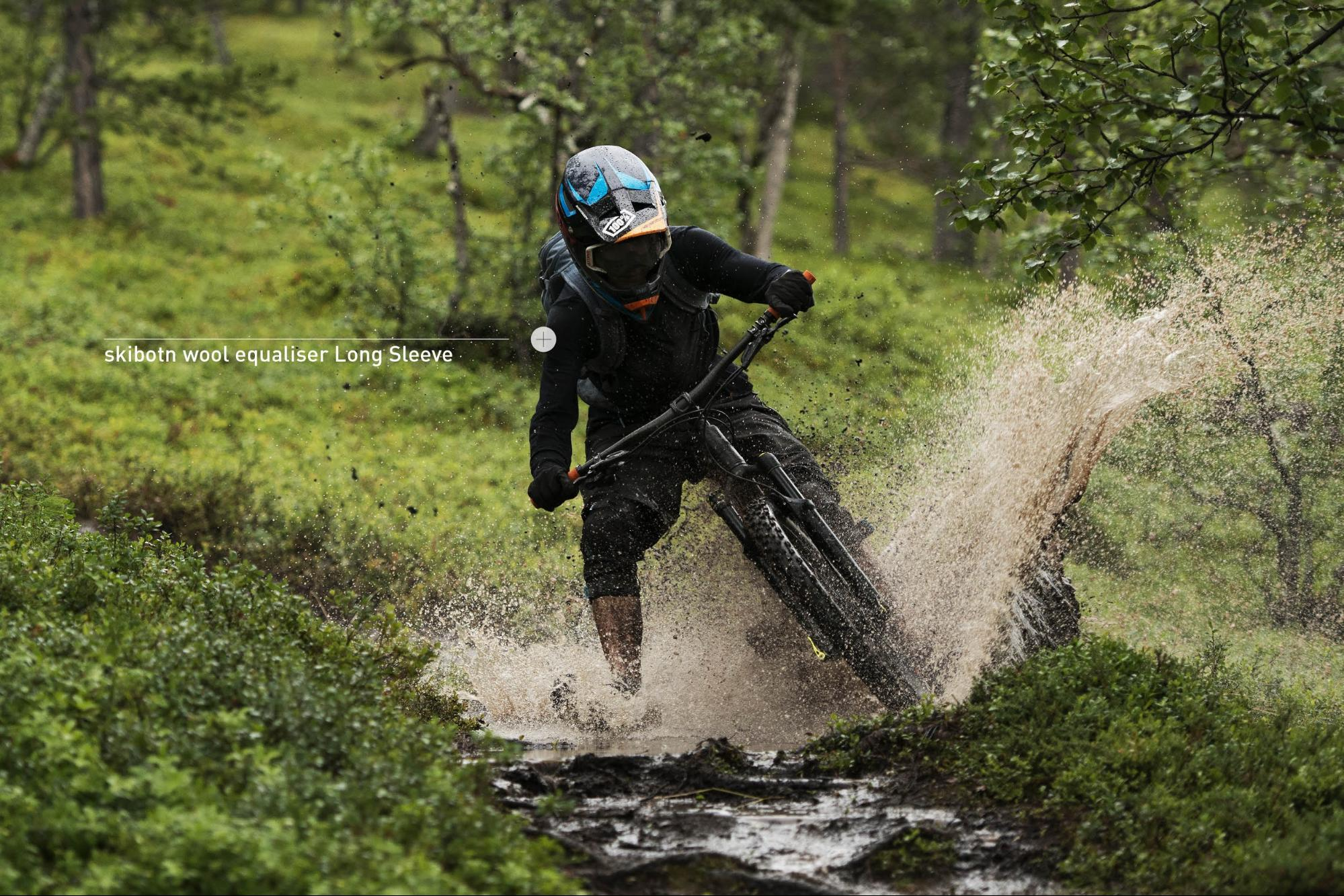 Mountain biker in a muddy turn wearing the skibotn equalizer Long Sleeve